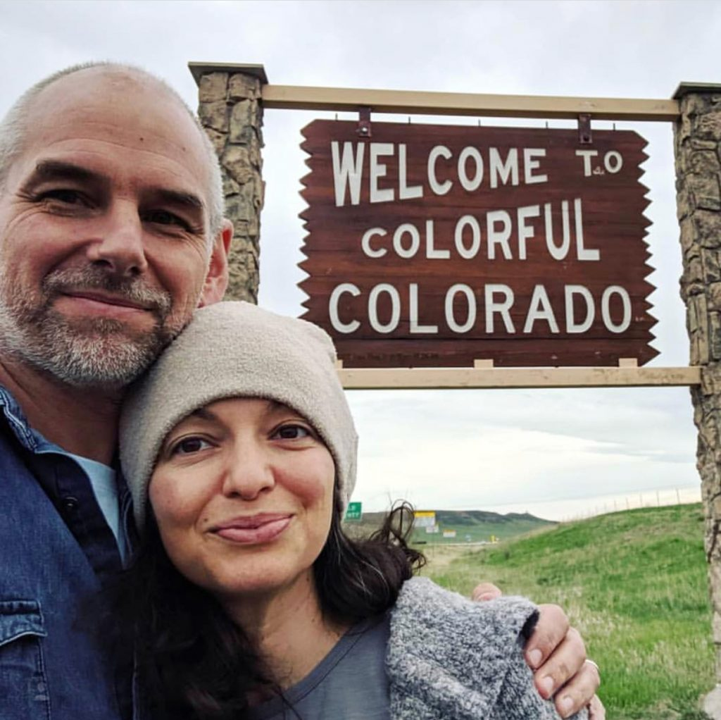 "authors Galina & Roland Denzel in front of a ""Welcome to Colorful Colorado"" sign"